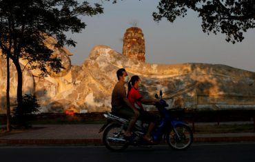 People ride a motorbike as they wear protective face masks amid the empty ancient temples usually crowded with tourists in Ayutthaya on March 30, 2020. (Reuters photo)